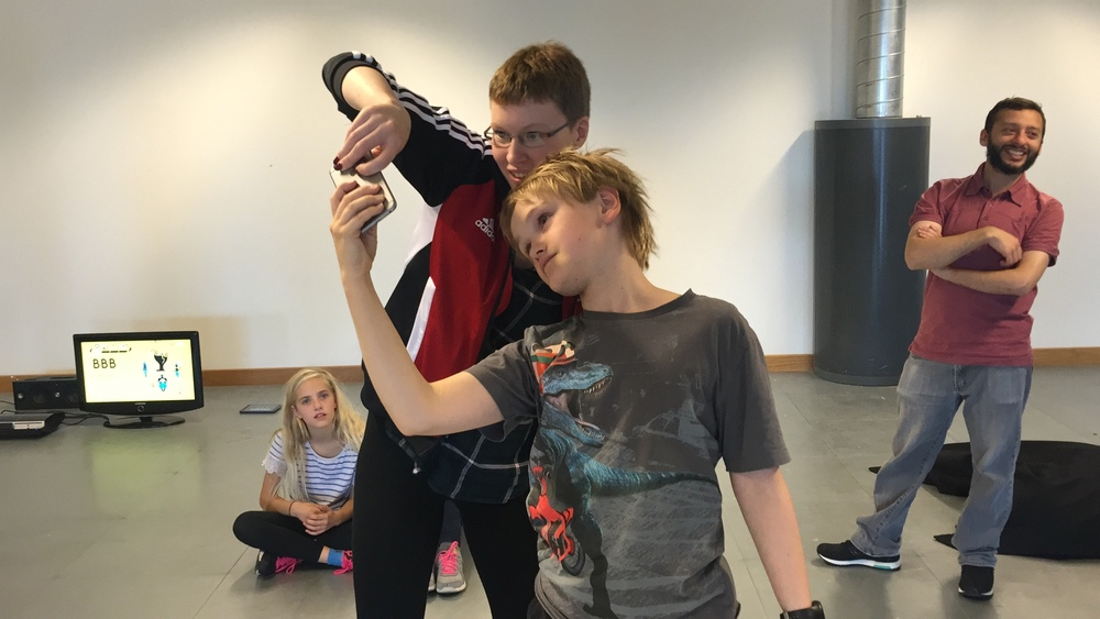 Some young participants taking part in a previous project. Here they are playing a digital game that requires you to move through the space whilst playing with a partner.