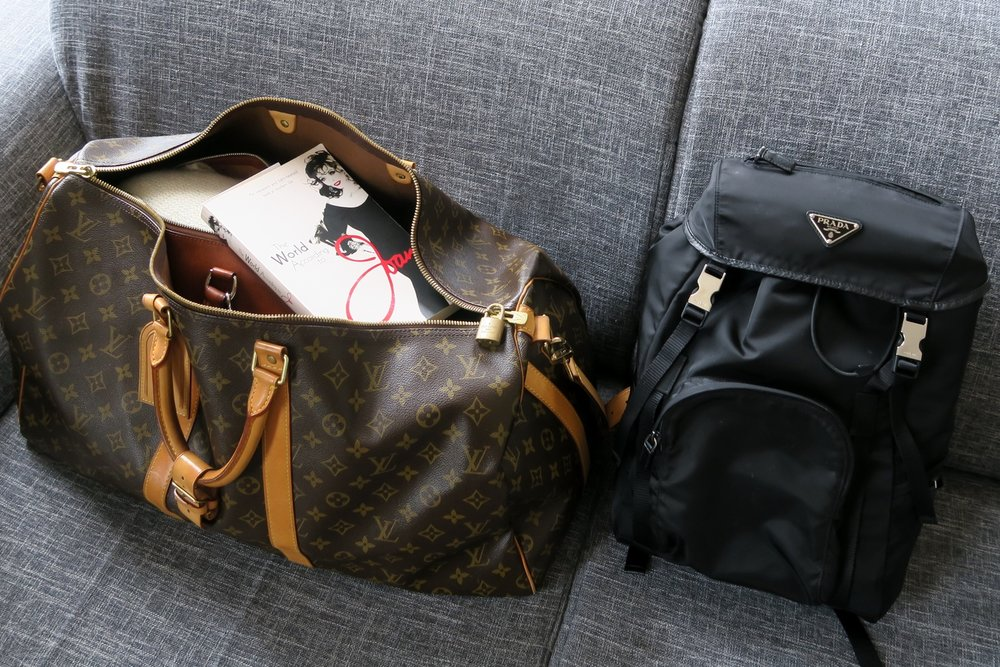 how-to-pack-light-for-your-flight-louis-vuitton-keepall-prada-back-pack-character-32-globetrotter-travel