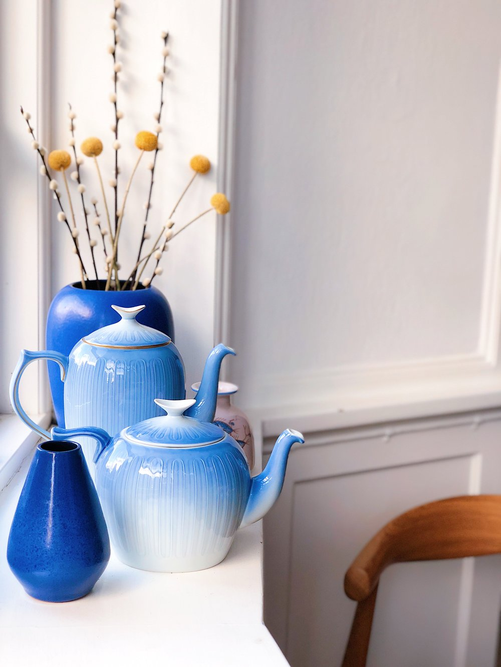 "The tea and coffee pots are Danish classics from Bing & Grøndahl, from a series known as ""Ballerina"", found secondhand online and at Brugtvare Terminalen. The smaller, blue vase was found at The Basement, while the larger one at the back was purchased alongside the tea pot at Brugtvare Terminalen."