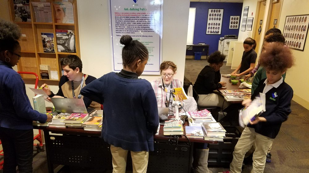 sixth grade student check out library books at Urban Pathways