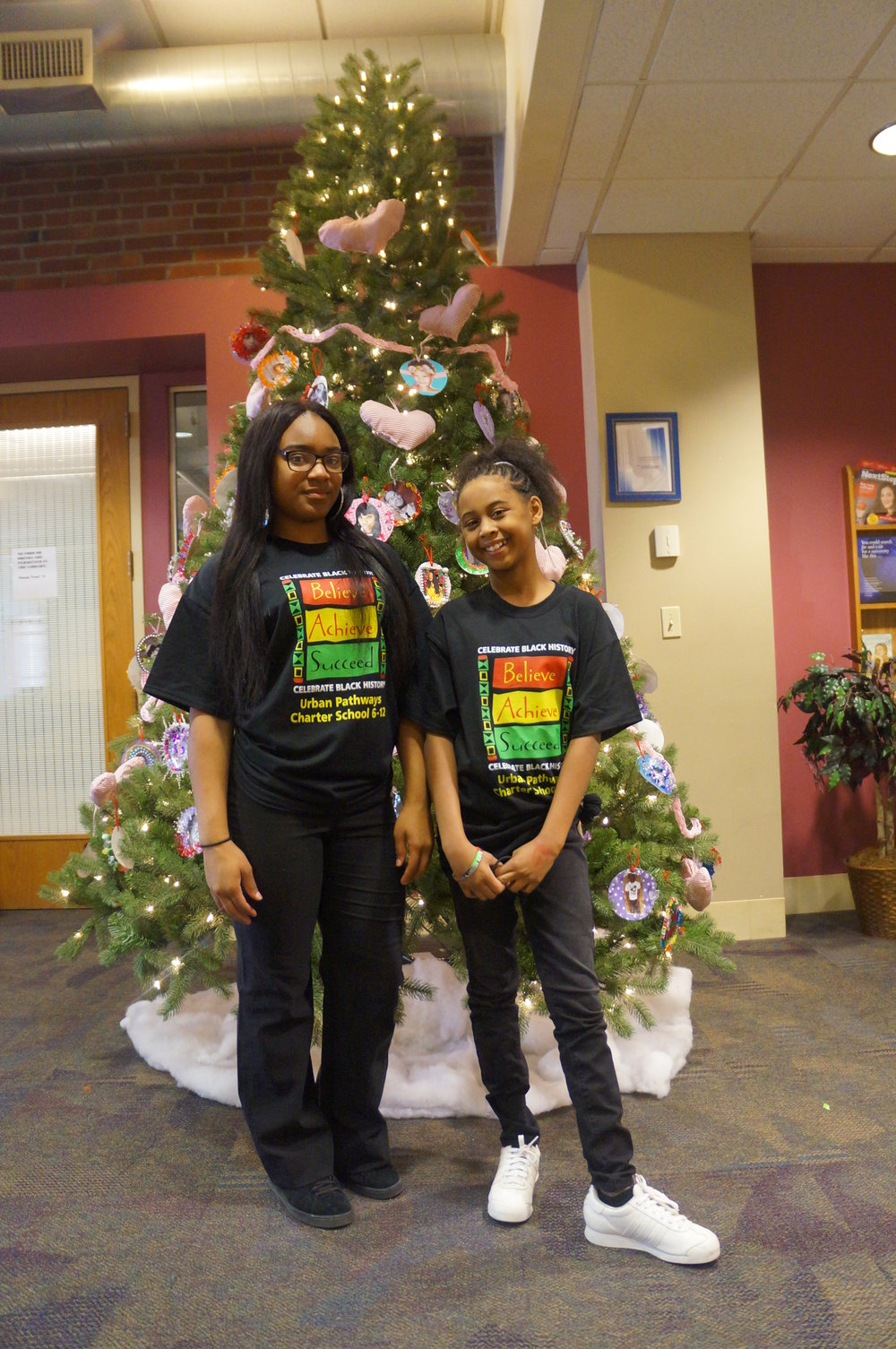 Urban Pathways students model the Black History Month t-shirt in front of our Black History Month tree.