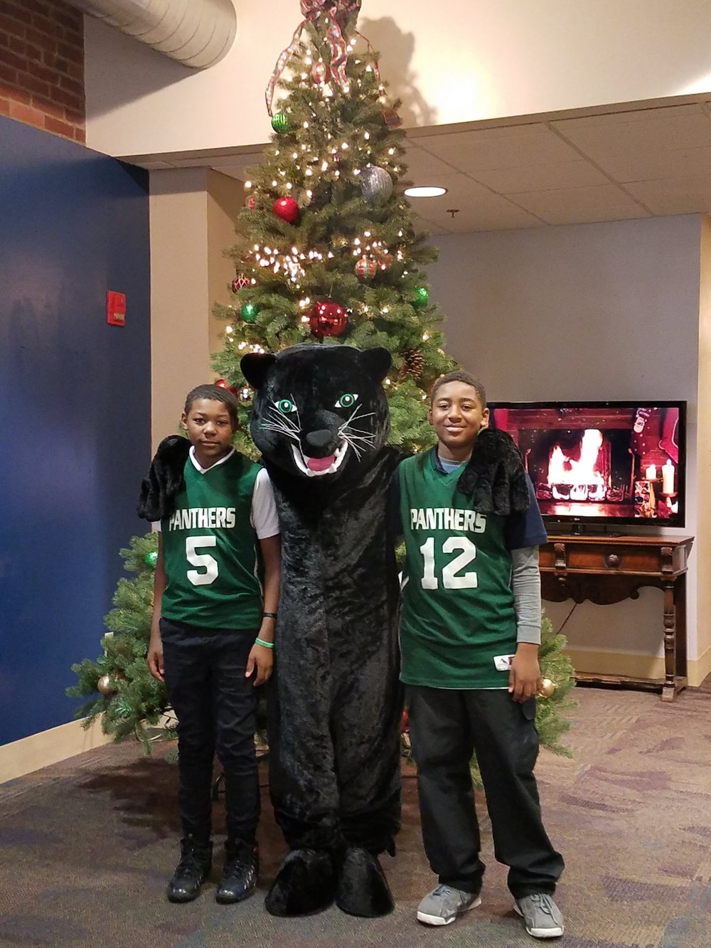 Urban Pathways Panther with basketball team members