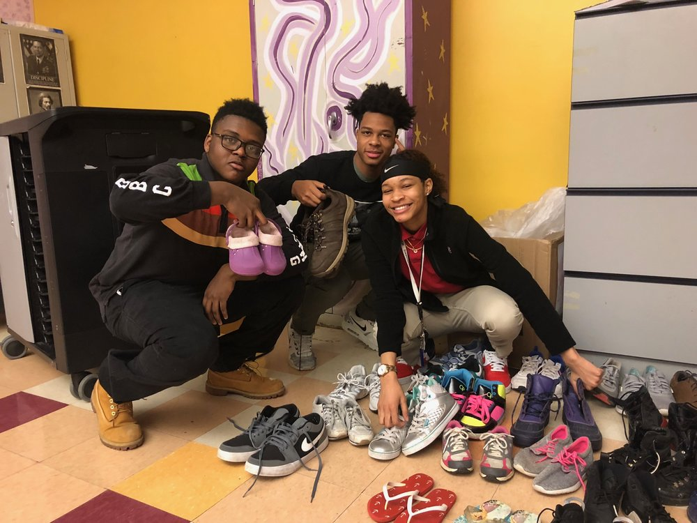 Urban Pathways seniors show the shoes collected in the Interact Club Show Drive
