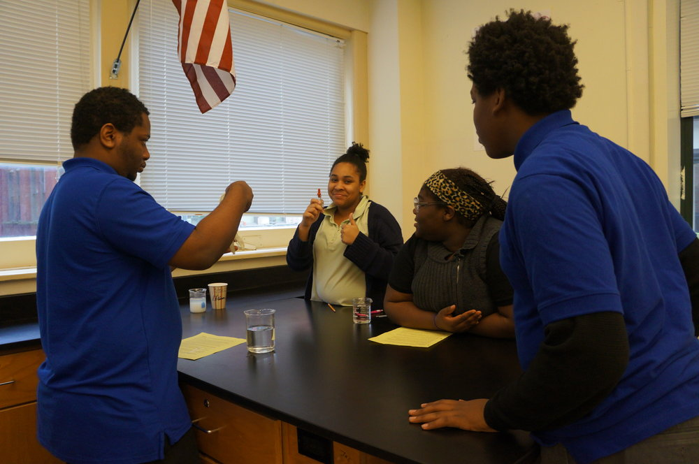 Iodine is diluted into a beaker of water in Urban Pathways biology lab