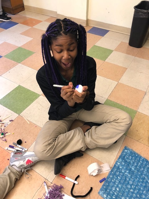 Urban Pathways 6th grader decorating and egg for the egg drop challenge