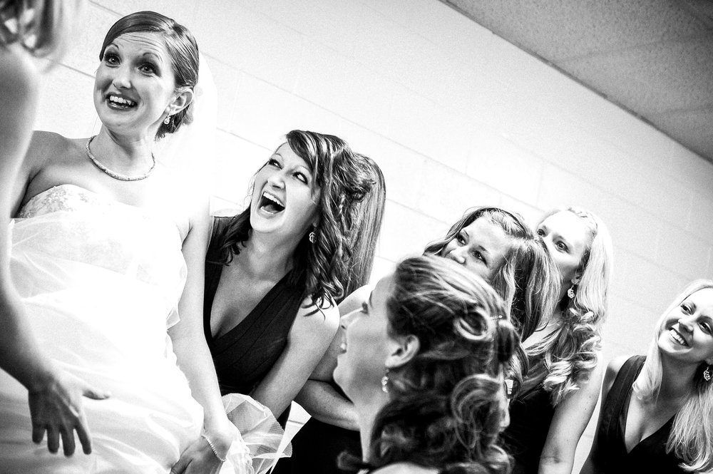 bride and bridesmaids laughing before wedding day