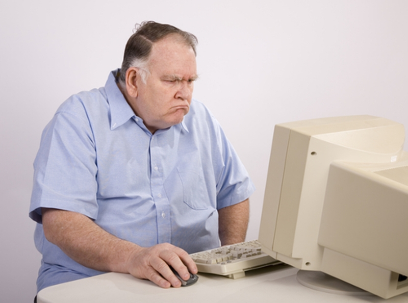 Frustrated man browses crappy posts on Facebook