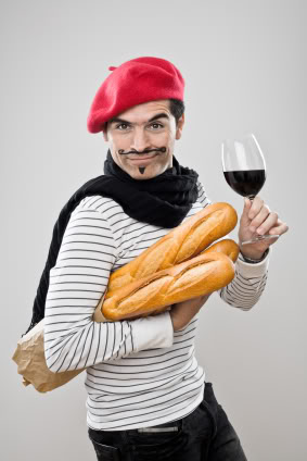 A frenchman walks home with 3 phagettes and a bottle of wine