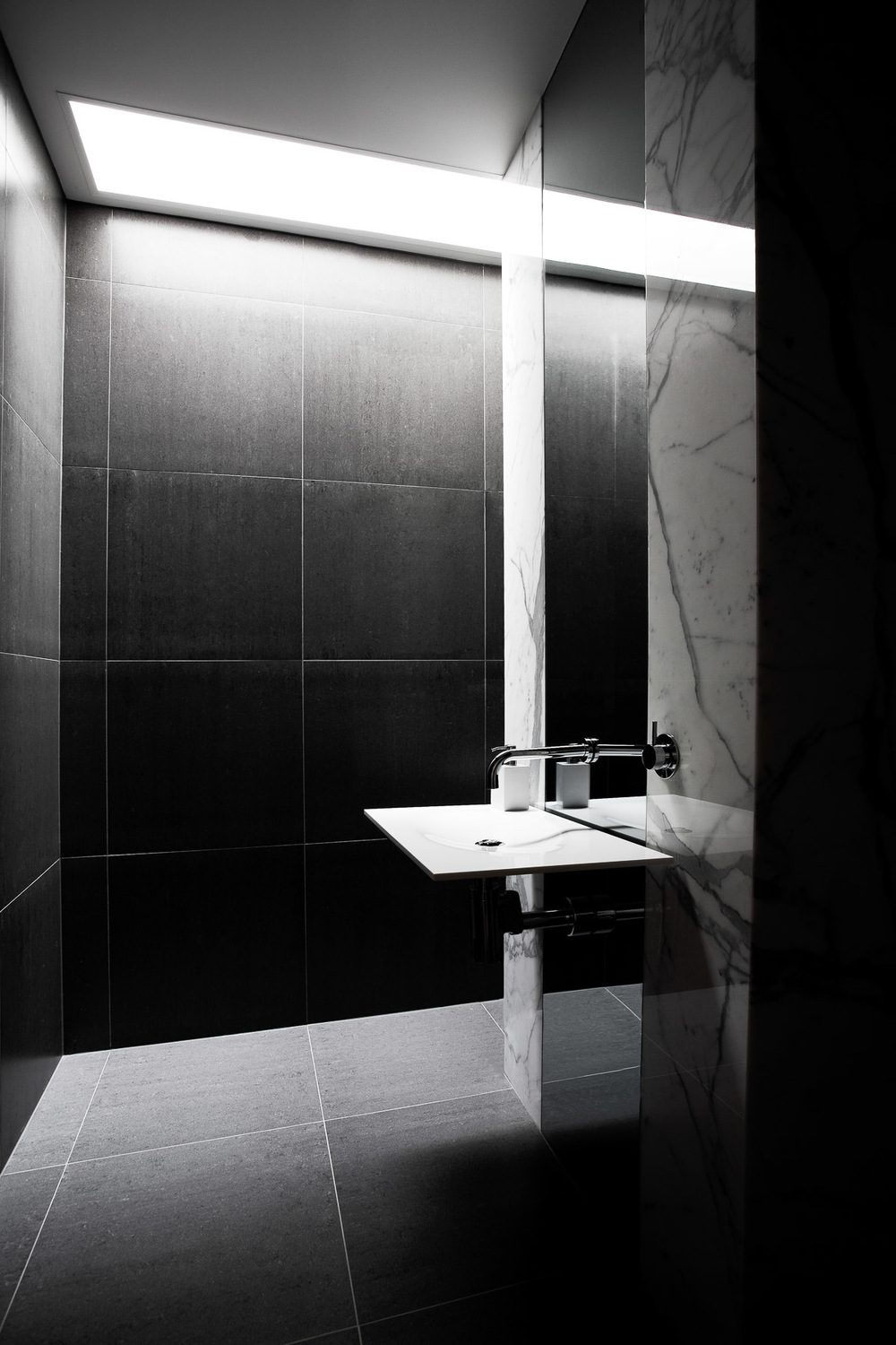 Bathroom with skylight and black tiles with marble wall over sink by Melbourne architecture photographer Stefan Postles