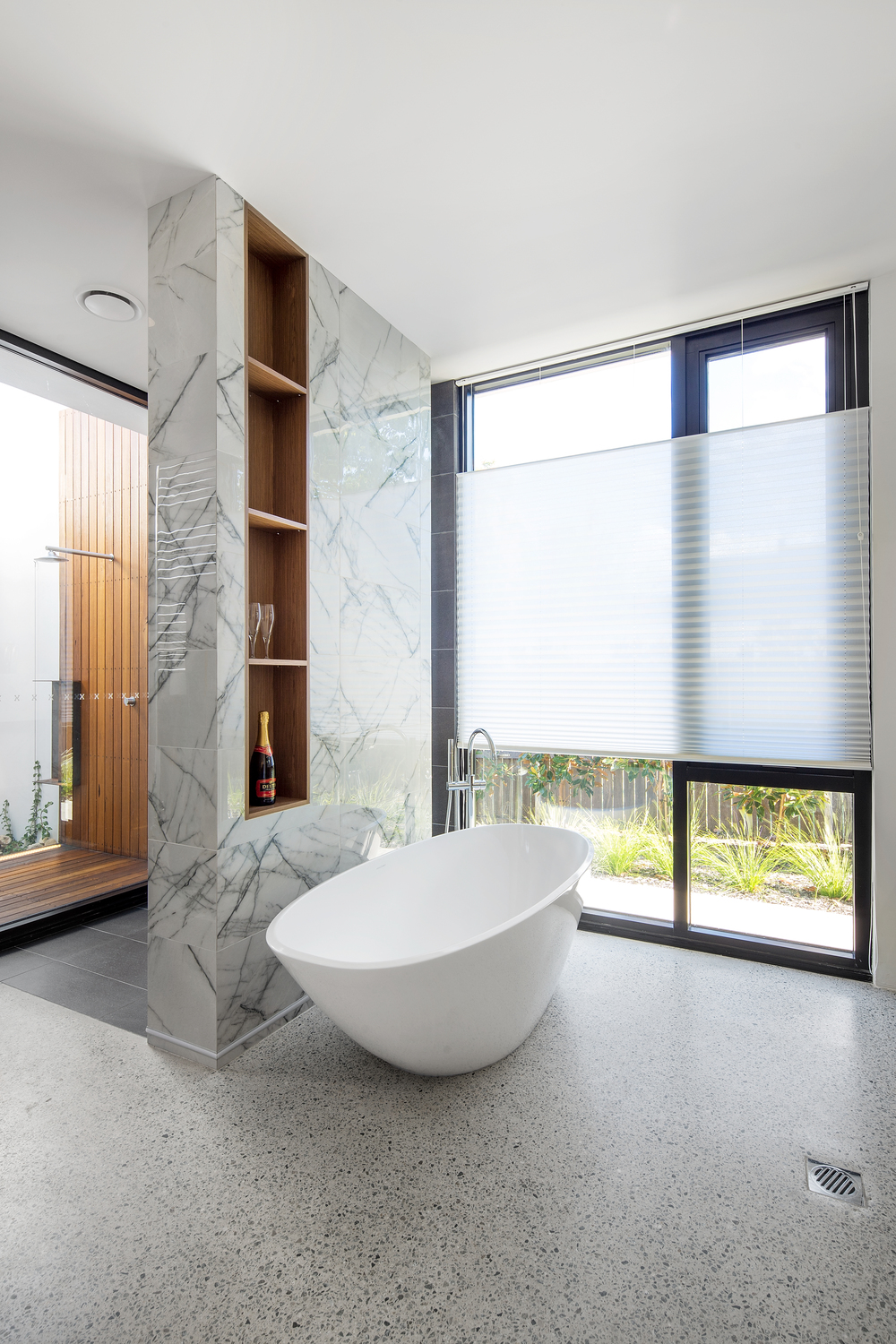 Modern bathroom with polished concrete floors and free standing bath by Melbourne architecture photographer Stefan Postles