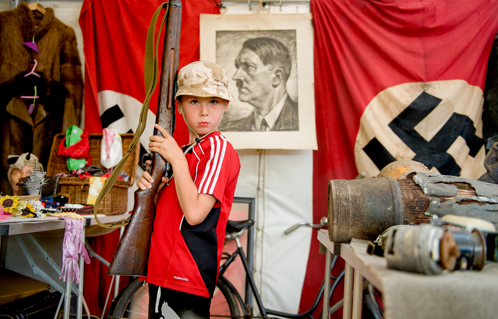 young visitor to War and Peach show posing with rifle, shot in a memorabilia tent selling original items from WW2.