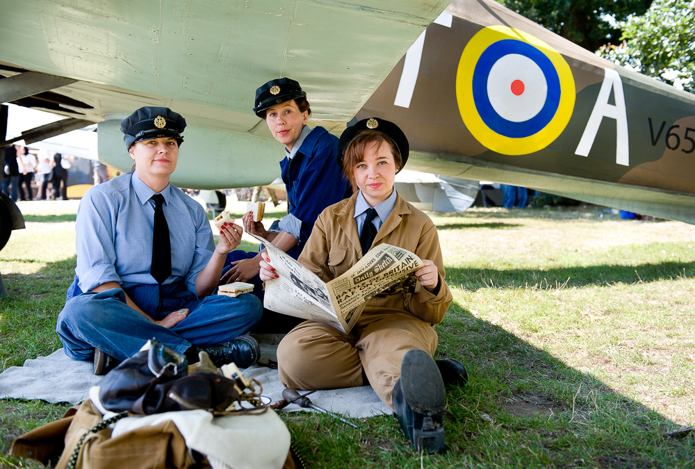 Re-enactors on lunch break under the wing of a WW2 fighter, War and Peace show, kent