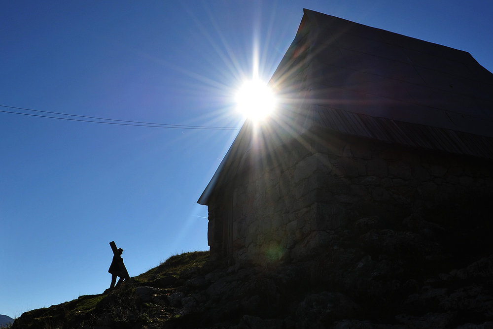 Silhouette of man and the house during the last warm sunny days in the Lukomir village where the villagers are preparing to leave the village before winter.