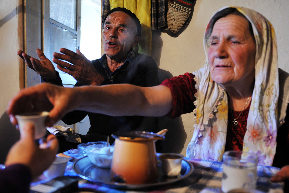 77 years old Ismet Comor speaks why they leave the Lukomir village while his wife Hatidza gives a cup of coffee to youngest son who has come to help them to get ready for the trip.