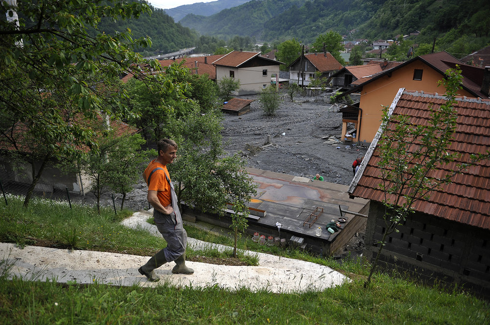 A man walks down the path after floods and landslides in the village of Topcic Polje near Zenica, 120 kms north of Sarajevo. Severe flooding in Bosnia has forced schools to close and hundreds of people to evacuate their homes and left thousands more without power.