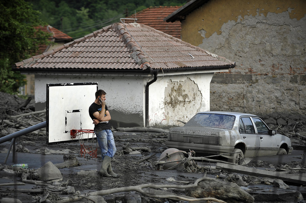 A man is standing on a flood-damaged basketball court in the village of Topcic Polje near Zenica.