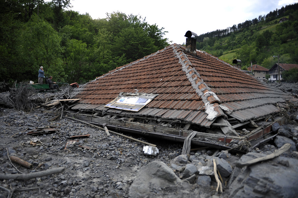 People pass by the house wich is buried in mud and rubble after a landslide at the village of Topcic Polje , near Zenica.