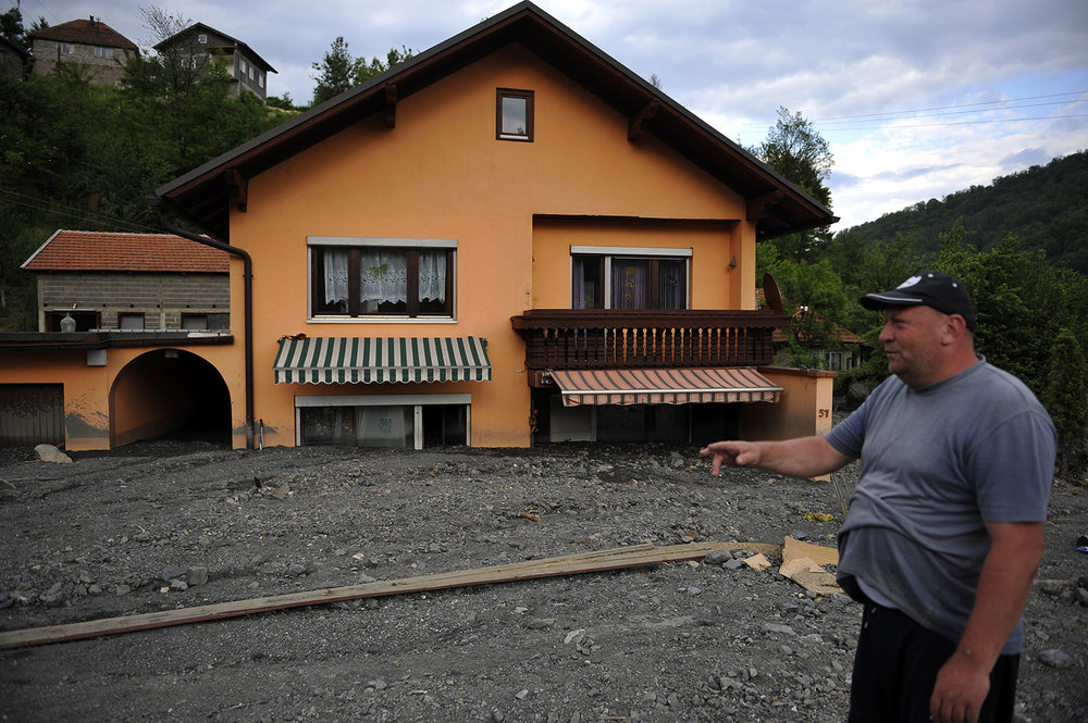 A man stands in front of his  house wich is   buried in mud and rubble after a landslide at the village of Topcic Polje ,   near Zenica.