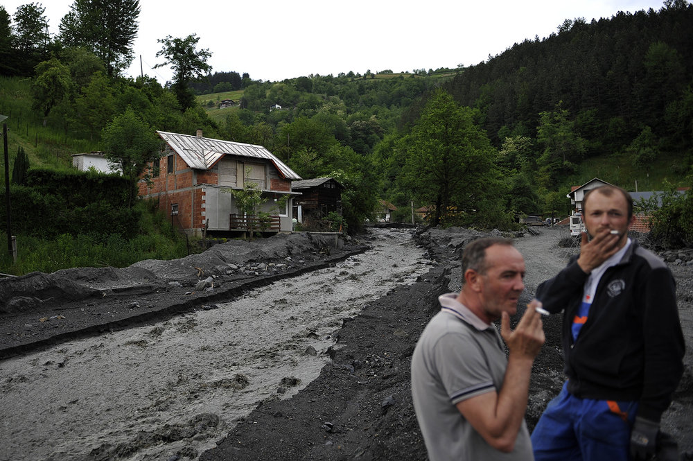 Two man stands near a landslide and floodwaters around houses in the village of Topcic Polje near Zenica.