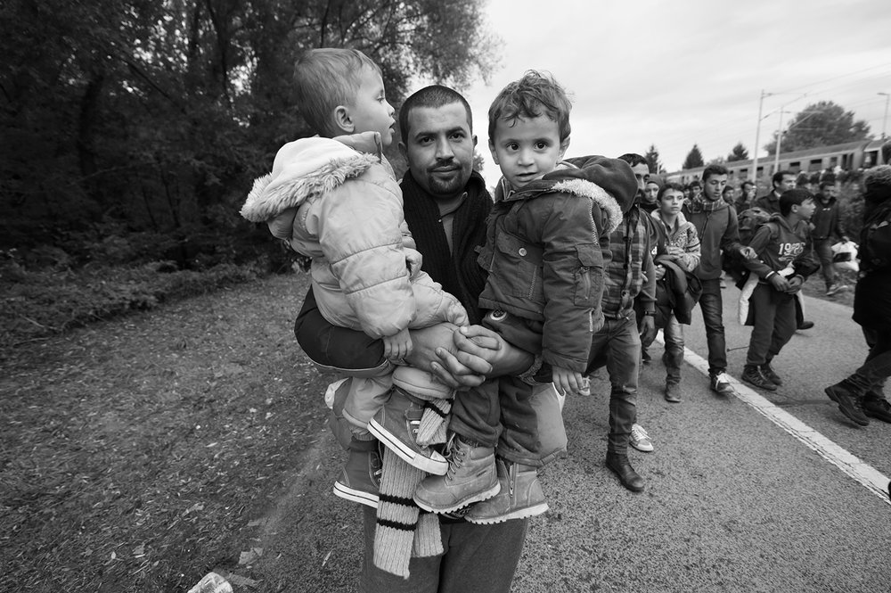 A man carries a children as he leave the railway station Botovo, near Koprivnica, Croatia. Several thousand refugees arrived by train and started to walk towards the Hungarian border, which will be closed after a few hours.