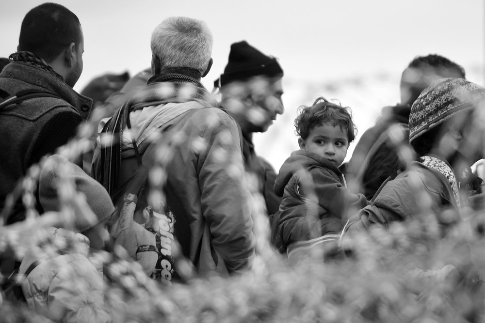View through barbed wire on a child and parents who cross into Hungary where they will continue to travel by train to Austria.