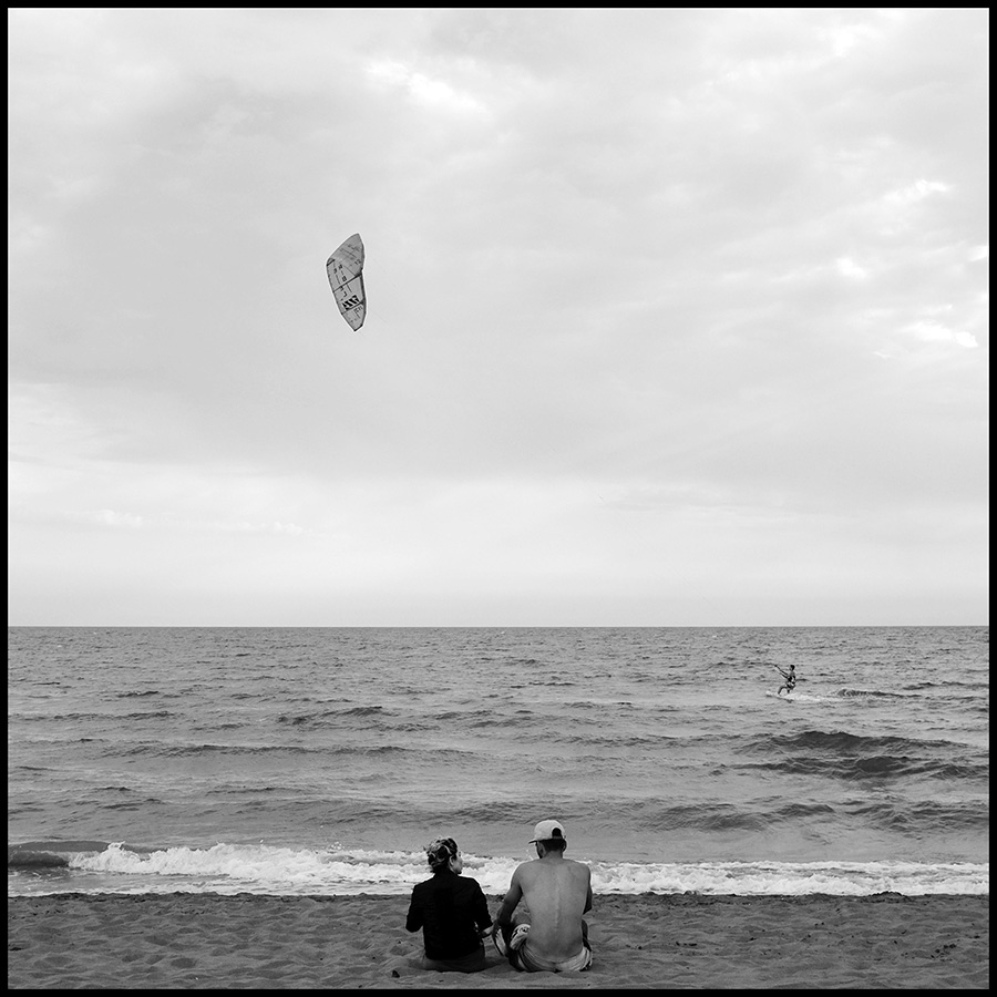 Couple watching kitesurfer performs on the Adriatic sea near Ulcinj, Montenegro.