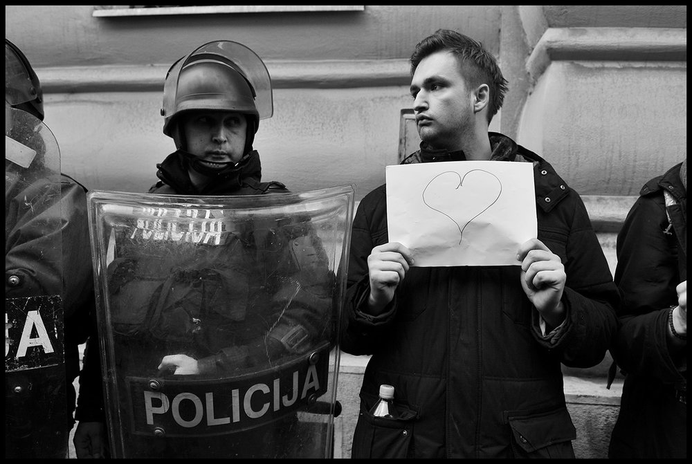 Bosnian young man standing next to a policeman and holds a banner with drawn heart during protest for the release of ten protesters in front of the Prosectors Office Building in Sarajevo. Several hundred people continued to protest in Sarajevo, demanding from politicians of all levels of government to resign. Street protests that erupted on February 7, a number of government buildings in several towns were ransacked and torched, while hundreds protestors and policemen were injured in scuffles.