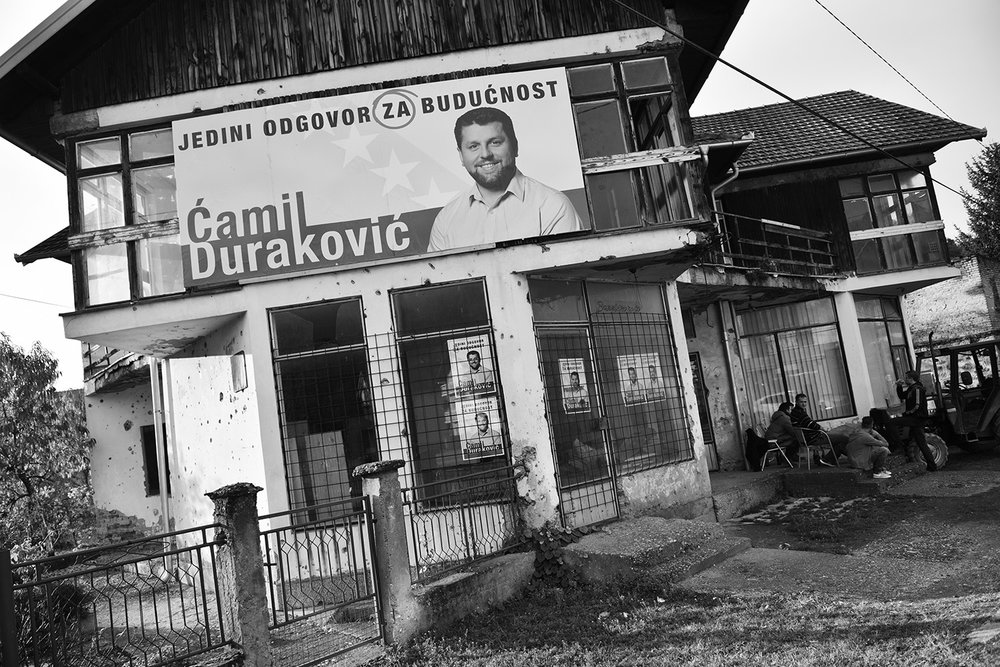 Election posters of current mayor of Srebrenica Camila Durakovic at the damaged house in Potocari, near Srebrenica. He had the unanimous support of Bosniaks, while the Mladen Grujicic was backed by all 10 local Serbian political parties and community groups. According to preliminary results from the October 2 election, Mladen Grujicic, is on track to become the town's next mayor. Some Bosniaks in municipality of Srebrenica believes that the election process was irregularity, but they are more afraid of will the new Mayor take care of the Memorial Center in Potocari where has buried more than 6,300 Bosniaks killed in genocide in July 1995.