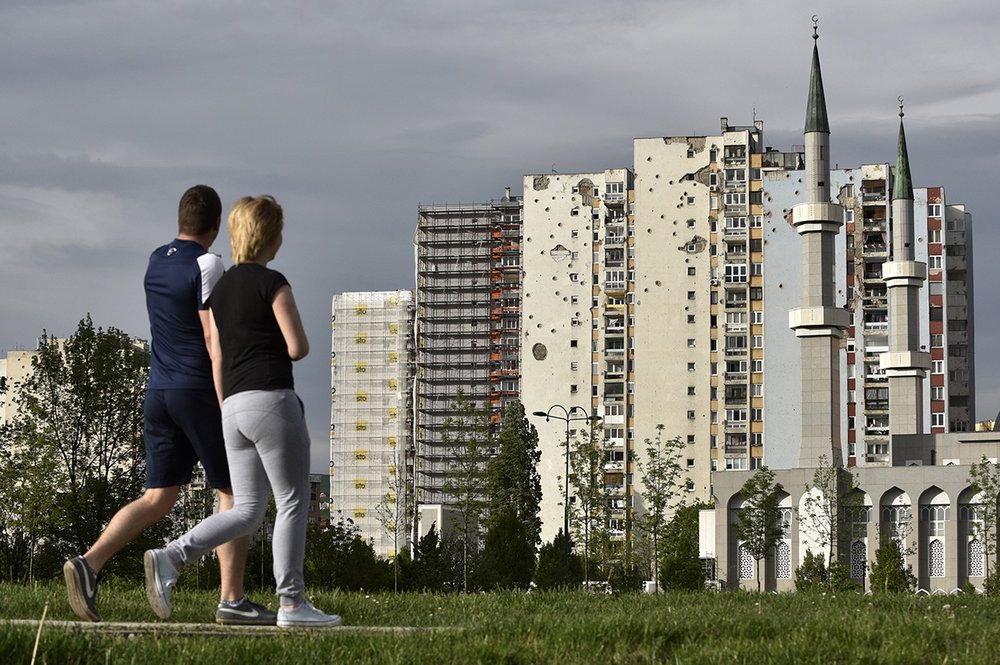 A young couple walks near the Alipasino Polje neighborhood in Sarajevo, where, 20 years after the war, devastation is still visible on residential buildings. Bosnia and Herzegovina