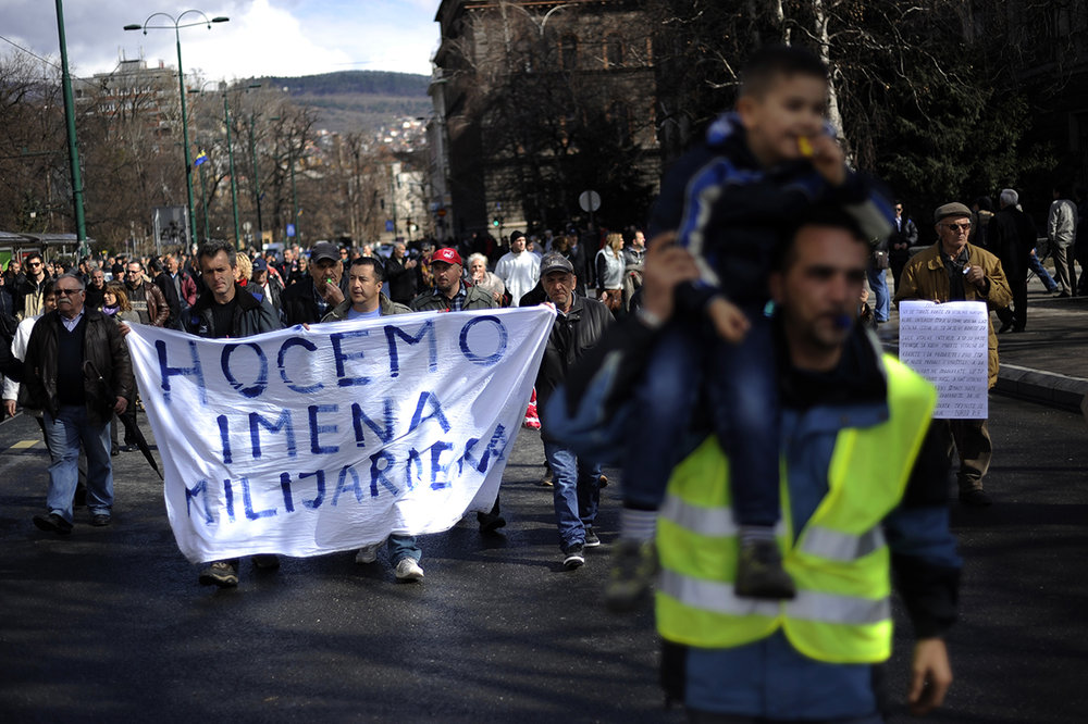 "Bosnian people protests with banner ""We want names of Millionaires""  in front of Bosnia and Herzegovina's Presidency building to block traffic at one of the busiest intersections of the country'scapital Sarajevo on February 20, 2014. Several hundred people continued to protest in Sarajevo, demanding from politicians of all levels of government to resign. Street protests that erupted on February 7, a number of government buildings in several towns were ransacked and torched, while hundreds protestors and policemen were injured in scuffles."