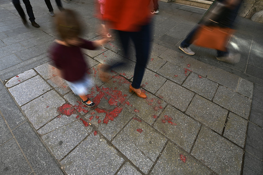 "People passing by a ""Sarajevo Rose"" in the BiH capital city. Throughout Sarajevo, concrete scars caused by mortar shell explosions have been filled with red resin as a memorial to those who lost their lives during the Siege of Sarajevo. Lasting 1,425 days, this was the longest siege of a capital city in the history of modern warfare. Bosnia and Herzegovina"