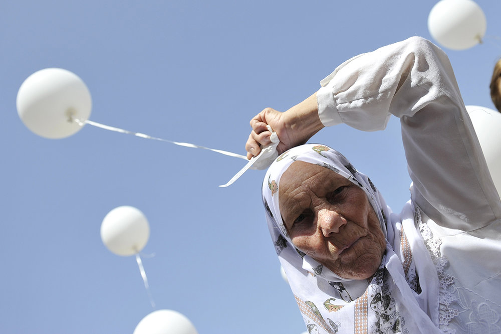 At a commemoration for the victims of the Omarska Concentration Camp, a mother releases a white balloon in memory of her son who was killed. During the Bosnian War, over 6,000 people were held in this camp, which is situated in northwestern Bosnia and Herzegovina.
