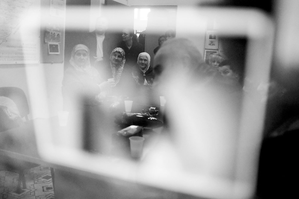 Reflection of Bosnian war survivors watching an online stream of Radovan Karadzic's verdict. After a 7-year-long trial, Karadzic was found guilty of genocide in Srebrenica, war crimes, and crimes against humanity and sentenced to 40 years in prison. Sarajevo, Bosnia and Herzegovina.