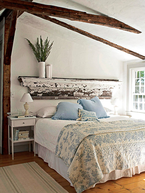 Distressed paint with exposed aged wood give this shelf-style headboard a charming and rustic cottage feel.
