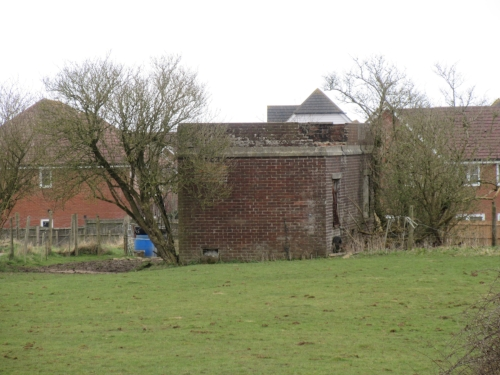 Fire tender building at former RAF Hawkinge in Kent. Virtually nothing remains of this historic airfield in the front-line during the Battle of Britain, other than the buildings housing the Kent Battle of Britain Museum. The housing beyond is built across the flying field. To the right of the tender building is a partly buried bulk aviation fuel store, this intended to provide protection during an attack. This last remaining part of the technical site is the focus of an application for further housing (June 2018).