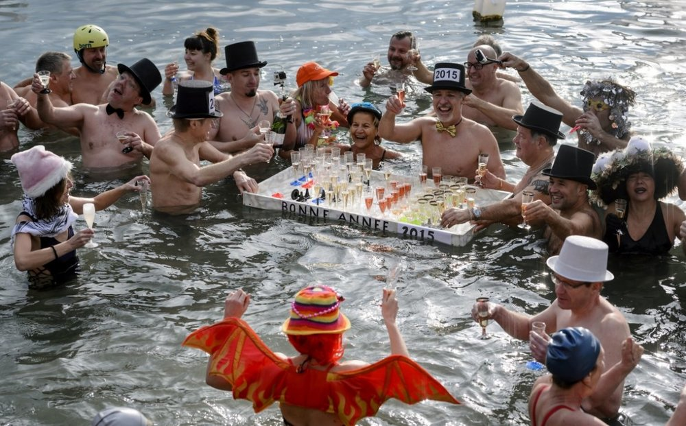 People hold glasses of champagne as they celebrate in the waters of Lake Geneva in Geneva, during the New Year's traditional bath, on 1 January 2015. Around 50 swimmers took part in the 21st edition of the traditional bath to mark the New Year.