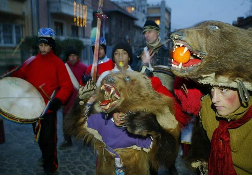 Two Romanian children dressed as bears dance with a band in Bucharest. Romanians dress themselves up with bear costumes during Christmas and New Year celebrations, to perform traditional dances believed to bring good luck and wealth in the next year.