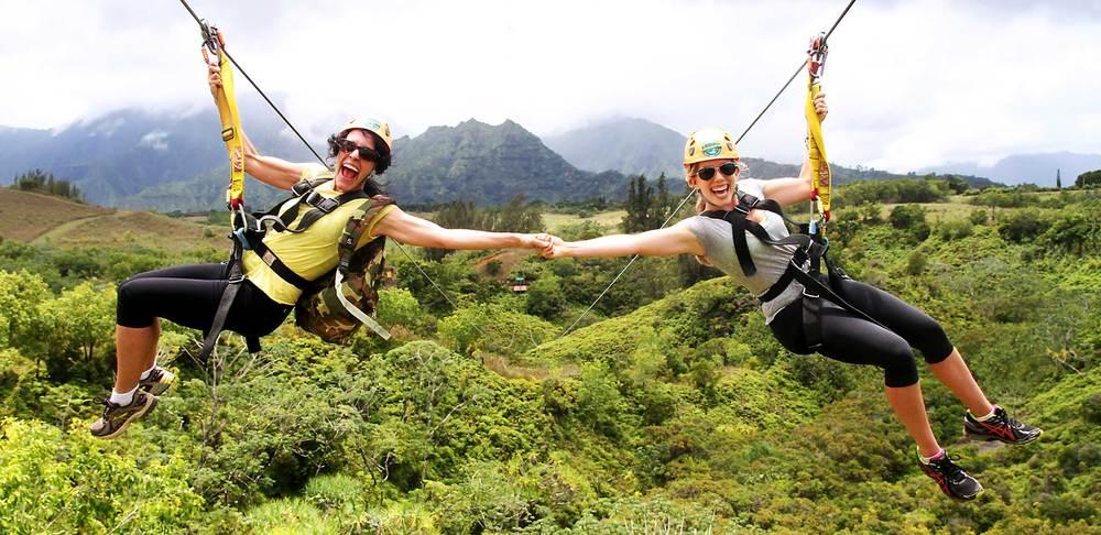 Customers smile as the fly down the King Kong line at Princeville Ranch Adventures, Kauai, HI.