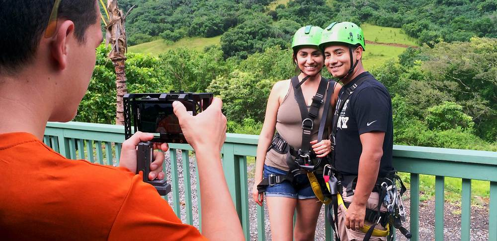 Zipline staff taking photos of a couple at Kualoa Ranch, Hawaii.