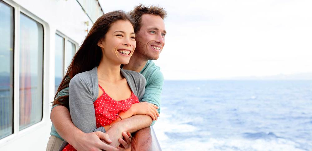 A couple has their picture taken while looking over the railing of the ship.