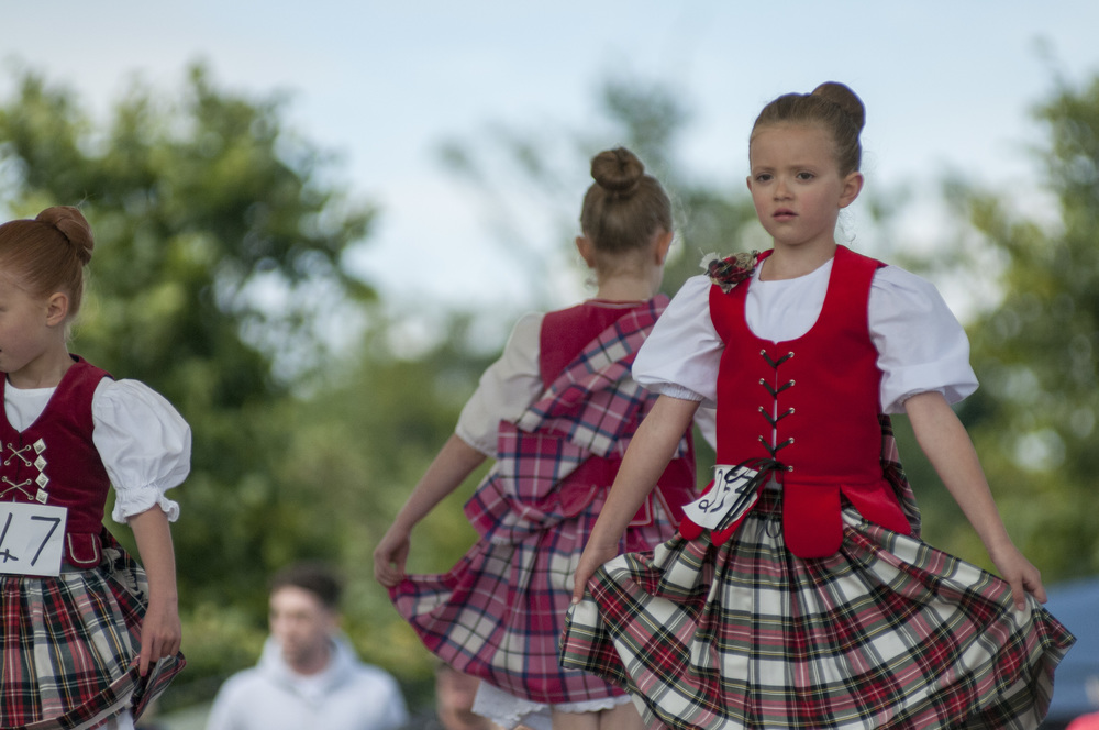 Scottish dancers perform a traditional dance in front of a table of judges at the St. Andrews Highland Games on July 26, 2015.