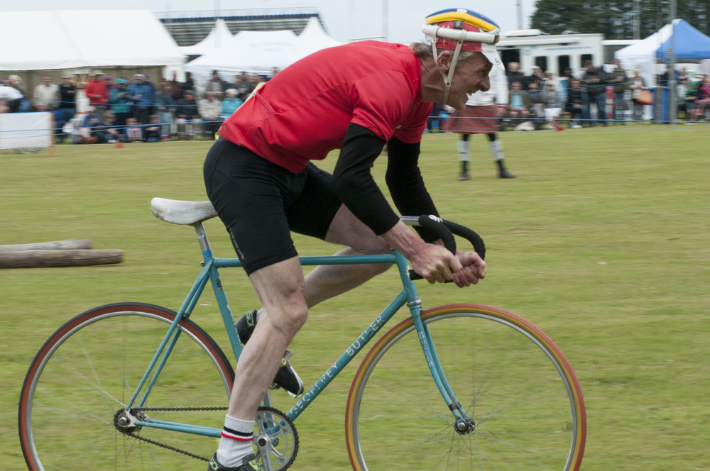 A cyclist competing at the St. Andrews Highland Games laughs as he rounds a turn on his last lap of the race on July 26, 2015 in St. Andrews, Scotland.