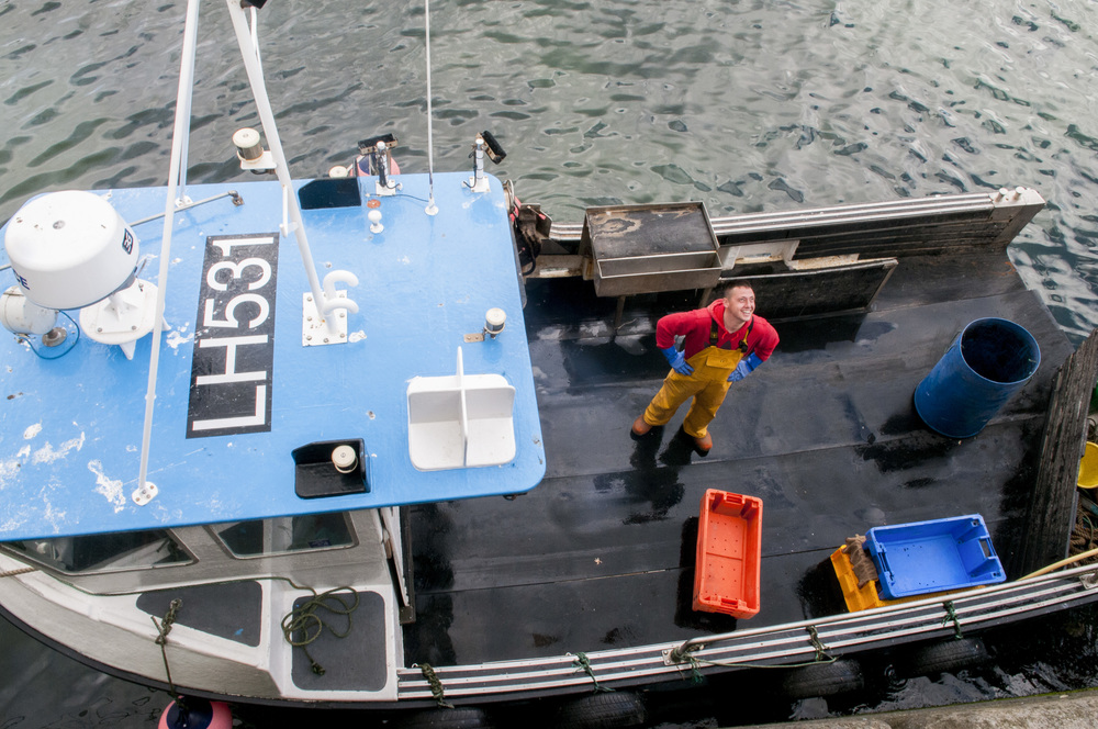 """Sean Fraser looks up from the deck of the """"Charlie Boy"""" after unloading the day's catch of lobster onto land in Dunbar, Scotland on July 23, 2015."""