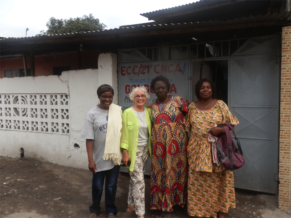 Maman Monique, Nancy Beatty & FEBA members outside property for the Women's Center