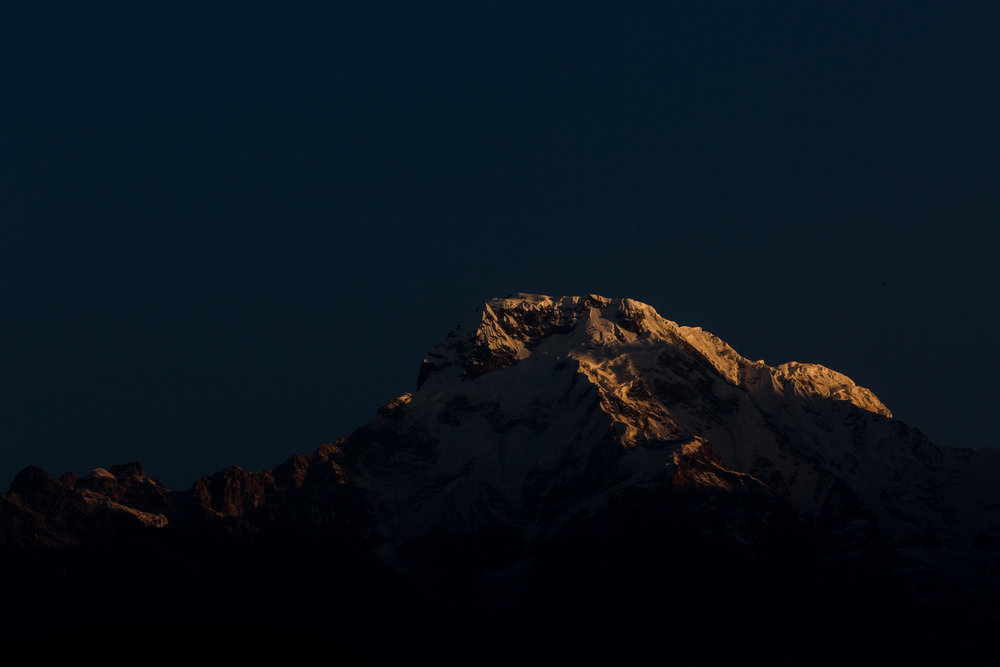The first sunlight at dawn reaches the summit of Annapurna South