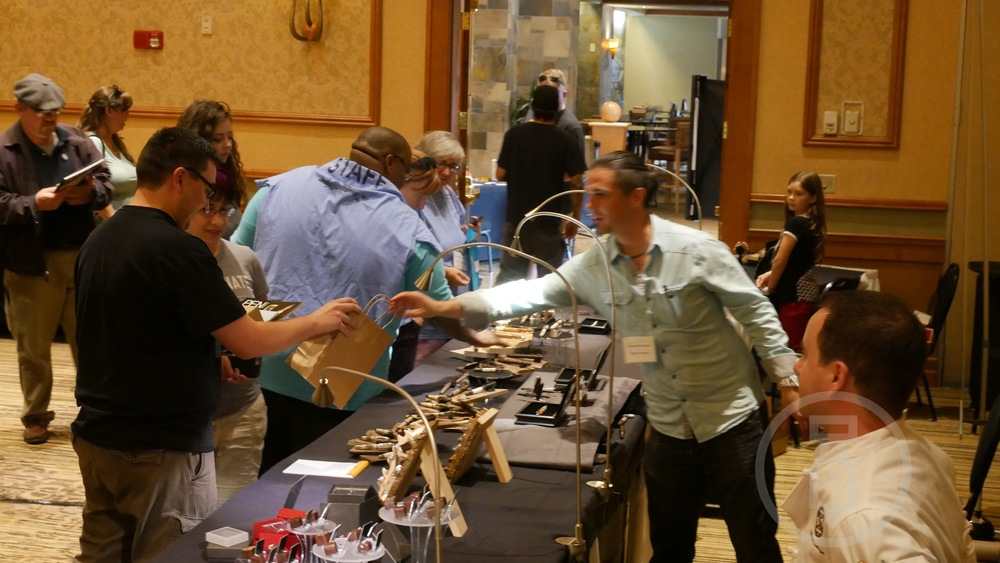Ryan Krusac handing a lucky winner a custom pen.