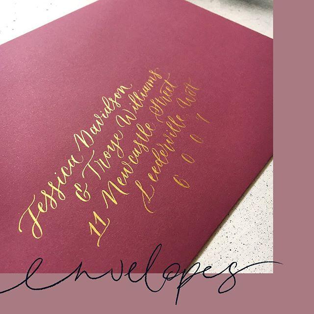 Gold calligraphy addresses on burgundy envelopes ✨