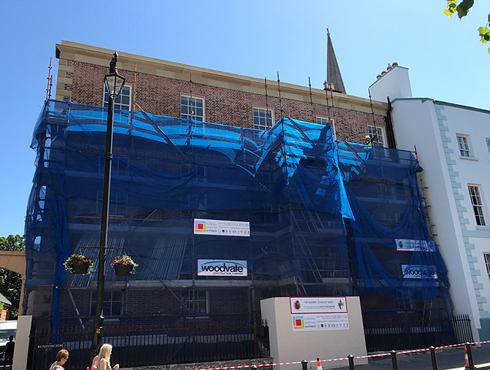 Scaffolding has started to be dismantled, revealing the refurbished facade with sandstone parapet and detailing restored