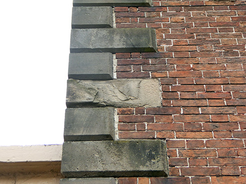 Before Restoration - Defective brick pointing and staining and damage to sandstone quoins