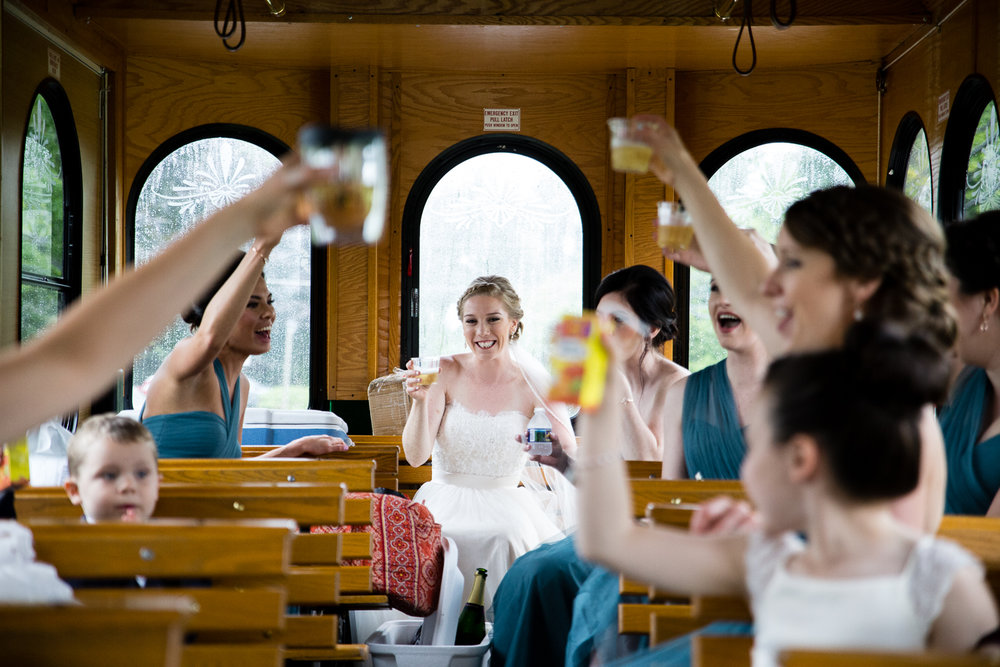 Bridesmaids toasting bride in trolley as they head towards church